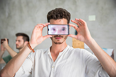 Man is holding smartphone with his eyes in front of his face  - p276m2110767 by plainpicture
