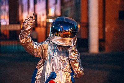 Spaceman in the city at night taking a selfie - p300m2043153 by Vasily Pindyurin