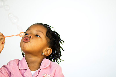 Young girl blowing bubbles - p3720395 by James Godman