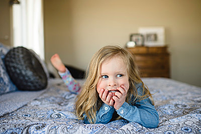 Girl lying on bed looking sideways - p429m1417634 by Erin Lester