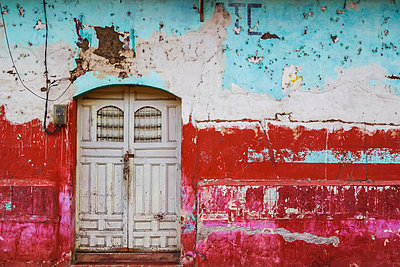 Worn and weathered facade of a building with peeling paint and double doors; Nicaragua - p442m1580589 by Henning Marstrand