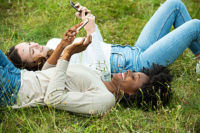 Young female friends lying on grass while using smart phone in park - p623m2294825 by Eric Audras