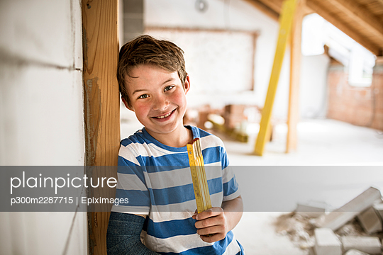 8 year old boy with broken arm on construction site in attic or loft during renovation with yellow folding rule, austria - p300m2287715 von Epiximages