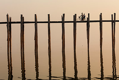 Two people cycling across tall teak bridge over a lake. - p1100m1520393 by Mint Images