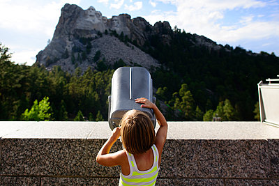 Rear view of girl looking through telescope at Mount Rushmore National Memorial - p1166m1474478 by Cavan Images