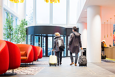 Rear view of business people with luggage walking at hotel lobby - p1264m1122120f by Astrakan