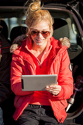 Young couple sitting in the back of a truck on tablet parked in parking lot - p1362m2163513 by Charles Knox