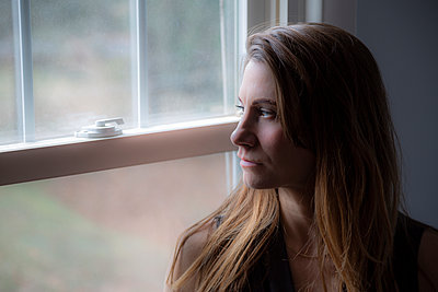 Serious young woman looking out window - p397m2044744 by Peter Glass