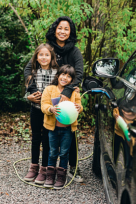 Portrait of smiling woman with daughters by electric car at charging station - p426m2194943 by Maskot