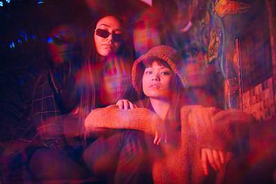 Multiple exposure of young female friends sitting together at illuminated restaurant - p426m2205270 by Maskot