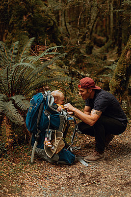 Hiker with baby exploring forest, Queenstown, Canterbury, New Zealand - p924m2098257 by Peter Amend