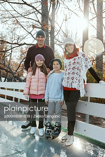 Family leaning on railing at the ice rink - p300m2081539 by Zeljko Dangubic