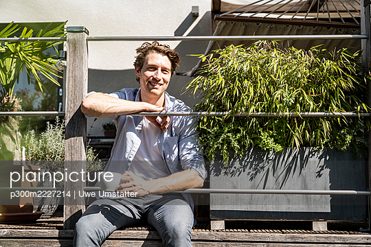 Smiling man with coffee cup sitting in balcony on sunny day - p300m2227214 by Uwe Umstätter