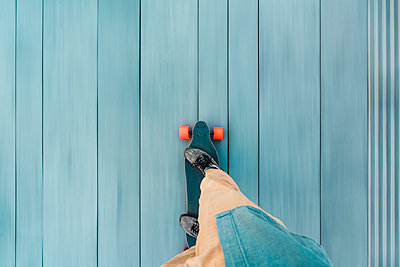 High angle view of man skateboarding on wooden floorboard in city - p1166m2066930 by Cavan Images