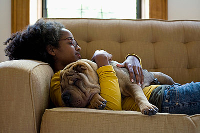 A young woman and her Shar-Pei napping on a couch - p3018224f by Winnie Au