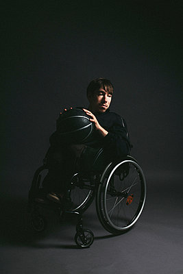 Male paraplegic athlete with basketball in wheelchair - p301m2213606 by Toby Mitchell