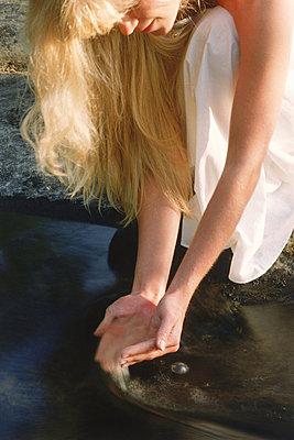 Blond woman dipping hands into small stream in Sweden - p34811177 by Chad Ehlers