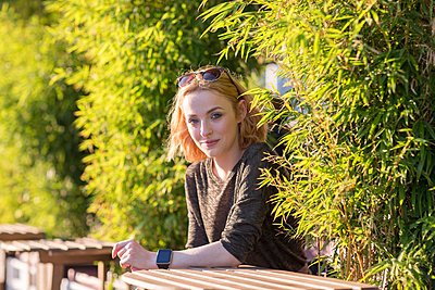 Young woman relaxing in cafe by river in summer - p429m2077826 by Tamboly