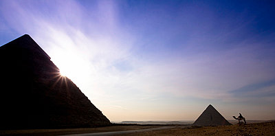 Two of the Pyramids with a traveller on a camel nearby - p4429320 by David DuChemin