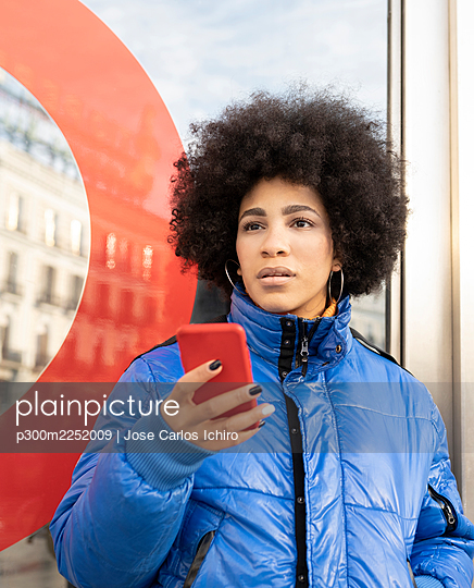 Afro young woman using mobile phone while standing at bus stop - p300m2252009 by Jose Carlos Ichiro