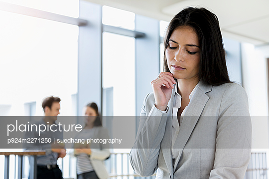 Germany, Bavaria, Munich, Young businesswoman standing in corridor - p924m2271250 by suedhang photography