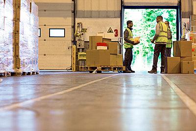 Workers talking in warehouse - p1023m820034f by Paul Bradbury