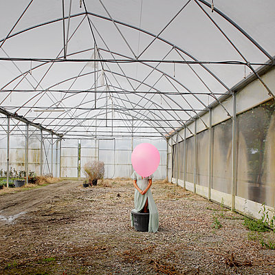 Woman with pink balloon in a greenhouse - p1105m2288793 by Virginie Plauchut