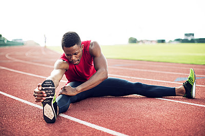 Sportsman touching toes while sitting on running tracks - p1166m1088126f by John Trice
