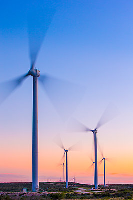 Wind turbines spinning during sunset - p1166m1547238 by Cavan Social
