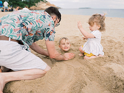 A young family enjoying a fun day on the beach during their vacation. - p1166m2152157 by Cavan Images