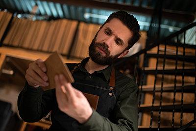 Male artisan examining leather handicraft - p1166m2234409 by Cavan Images