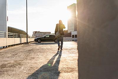 Mature man walking on parking level to his car, talking at the phone - p300m2023746 von Uwe Umstätter