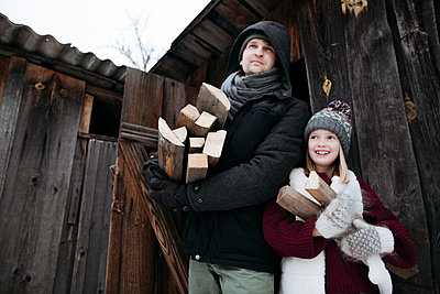 Happy father and daughter holding firewood in winter - p300m2160465 by Ekaterina Yakunina