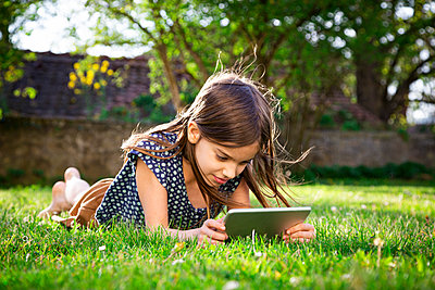 Smiling girl lying on meadow in the garden using digital tablet - p300m2189307 by Larissa Veronesi