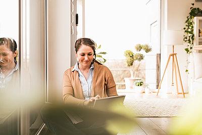 Smiling female entrepreneur wearing headphones using digital tablet - p300m2267554 by Uwe Umstätter