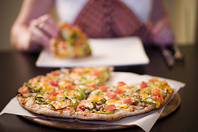 Woman eating pizza, front view - p4422660f by Design Pics