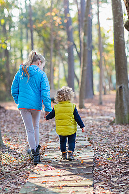 Caucasian brother and sister walking on wooden walkway - p555m1413795 by Marc Romanelli