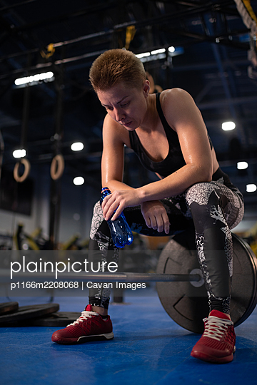 Exhausted sportswoman drinking water on barbell - p1166m2208068 by Cavan Images