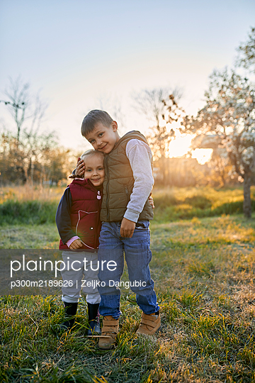 Affectionate brother and sister standing on a meadow at sunset - p300m2189626 by Zeljko Dangubic