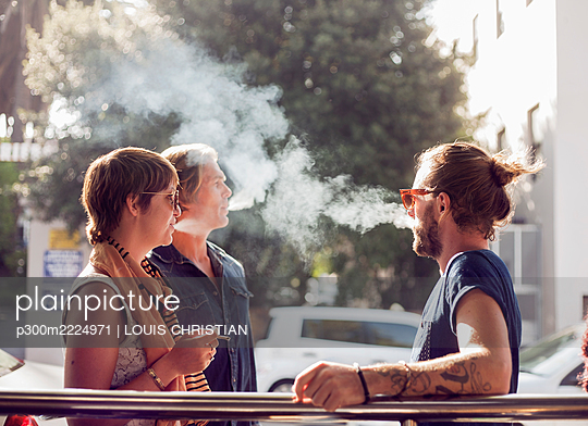 Friends smoking while standing outdoors on sunny day - p300m2224971 by LOUIS CHRISTIAN