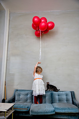Mädchen mit Luftballons im Wohnzimmer - p1212m1092000 von harry + lidy