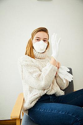 Portrait of blond woman wearing FFP2 mask at home - p300m2188587 by Sandra Bielmeier