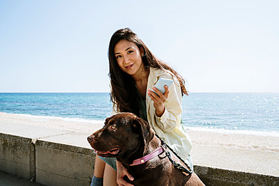 Smiling woman sitting with Labrador Retriever by sea - p300m2273518 by VITTA GALLERY
