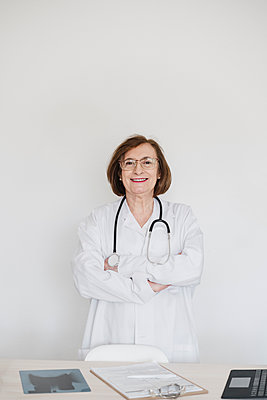 Smiling female doctor with arms crossed standing in front of desk at hospital - p300m2274503 by Eva Blanco