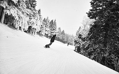 Snowboarder riding down at trail - p343m1446595 by Josh Campbell