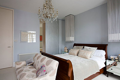 Wooden bed with sofa and mirrored bedside cabinets in London home  UK - p3493525 by Robert Sanderson