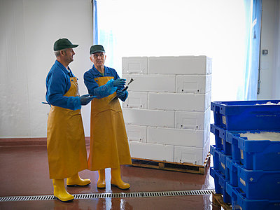 Workers with pallets in warehouse - p42917324f by Monty Rakusen