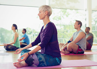 Serene woman in lotus position in yoga class - p1023m1127522f by Sam Edwards