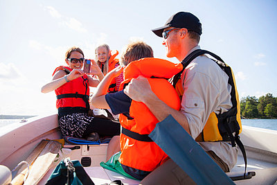 Woman photographing man and son on boat - p426m844638f by Katja Kircher