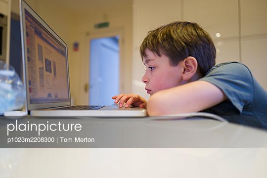 Boy homeschooling at laptop - p1023m2208300 by Tom Merton